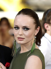 Laura Haddock added drama to her khaki dress with a pair of green feathered dangle earrings.