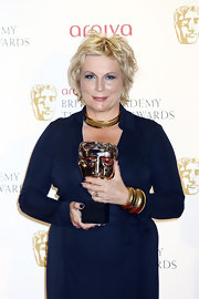 Jennifer Saunders glammed up a subdued dress with gold bangles.