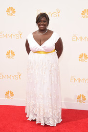 Retta donned a white gown featuring a lace skirt, a yellow sash, and a cleavage-revealing neckline to the Emmys.