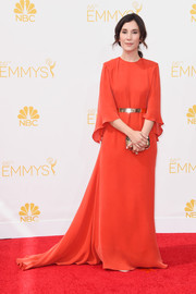 Sibel Kekilli cut a regal figure at the Emmys in a flowy red gown with cape-like detailing and a long train.