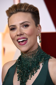 Scarlett Johansson contrasted her glamorous outfit with a punky boy cut during the Oscars.