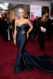 For the Oscars, Rita Ora got glammed up Old Hollywood style in a strapless midnight-blue Marchesa mermaid gown with gold accents along the neckline and waist.
