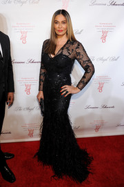 Tina Knowles worked the Angel Ball red carpet in a black lace-panel mermaid gown with a feathered skirt.