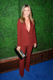 Jennifer Aniston paired a black and gold leather foldover clutch with a red pantsuit for the Critics' Choice Movie Awards.