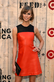 Karlie Kloss complemented her sophisticated leather dress with a simple black patent leather clutch at the Feed USA + Target launch.