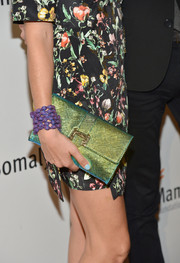 Rebecca Minkoff sported a vibrant mix of colors at the Life is Love Gala with this metallic green clutch, purple bracelet, and floral dress combo.