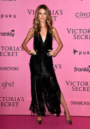 Behati Prinsloo channeled the roaring '20s with this sparkly black halter dress, featuring a fringed skirt and a plunging neckline, during the Victoria's Secret after-party.