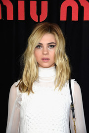 Nicola Peltz styled her hair with messy-sexy waves for the Miu Miu fashion show.