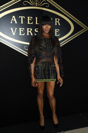 Naomi Campbell put her toned pins on display in a super-short multicolored embroidered frock by Atelier Versace during the label's fashion show.
