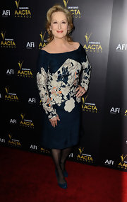 Meryl took to the red carpet in a navy blue off-the-shoulder dress complete with a chic floral print.