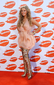 Delta Goodrem pairs her peachy mini dress with these over-the-top gold boots with lace-up backs.
