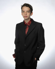 At the Australians in Film's 2011 Breakthrough Awards, Kodi Smit-McPhee posed for a portrait wearing a black three-button blazer over his orange-and-black shirt.