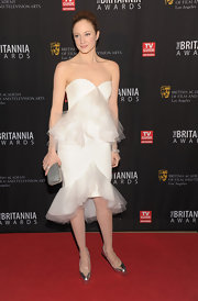 Andrea Riseborough added subtle contrast to her stunning tulle-adorned dress with a slate snakeskin hard case clutch.