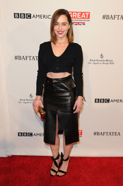 Emilia Clarke paired a long-sleeved black croptop with an edgy leather skirt to complete her head-to-toe look.