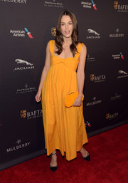 Going the matchy-matchy route, Keira Knightley accessorized with a marigold Roger Vivier Prismick Mini Beads clutch.