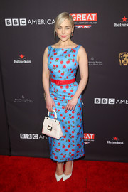 Emilia Clarke pulled her chic look together with a striped top-handle purse by Roger Vivier.