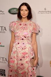 Caitriona Balfe paired a pearlized box clutch by Edie Parker with an embroidered dress for the BAFTA Los Angeles Tea Party.