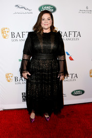 Melissa McCarthy added a hint of color with a pair of purple velvet pumps.