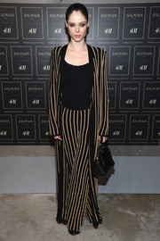 Coco Rocha was rocker-glam in an ankle-length gold and black striped coat and matching pants during the Balmain x H&M collection launch.