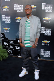 B.o.B paired his gray tack jacket and striped shirt with white low top sneakers.