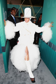Erykah Badu complemented her coat with white platform boots, also by Thom Browne.
