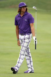 Rickie dons some purple plaid Puma pants and matching purple attire on the golf green.
