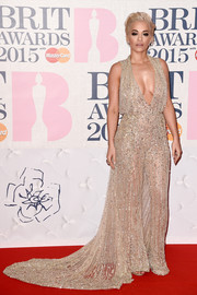 Rita Ora sparkled in a fully bejeweled gown with a risque plunge at the BRIT Awards.