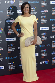 Kelly Holmes chose this pastel yellow dress for her chic and elegant red carpet look at the BT Sports Industry Awards.