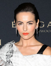 Bright orange lipstick provided a dazzling pop of color to Camilla Belle's look.
