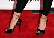 The tattoo clad actress sported a sexy pair of satin peep-toed pumps with her black leggings. These classic heels are perfect for an elegant evening event.