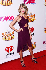 Taylor Swift attended Z100's Jingle Ball looking more daring than usual in a burgundy one-shoulder cutout dress by Reem Acra.