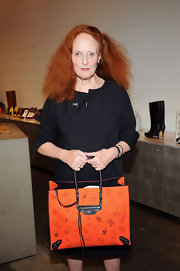Grace Coddington flaunted a stylish orange cat print Balenciaga tote handbag at the Fashion's Night Out party.