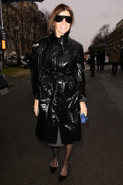 Carine Roitfeld covered up in edgy style with a black patent leather coat for the Balenciaga fashion show.