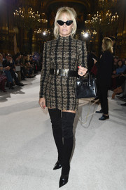 Pamela Anderson cut a strong silhouette in this bold-shouldered tweed dress by Balmain during the brand's fashion show.