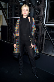 Sofia Richie spiced up her plain black jumpsuit with a multicolored tweed coat, also by Balmain.