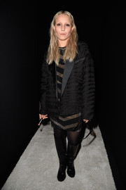 Noomi Rapace amped up the edgy feel with a pair of black knee-high boots.