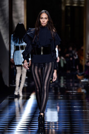 Joan Smalls looked conservative up top in a long-sleeve black ruffle blouse while walking the Balmain show.