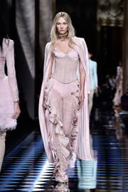 Karlie Kloss looked provocative in a pink corset top while walking the Balmain fashion show.