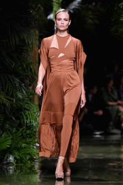 Natasha Poly looked fierce in an asymmetrical rust-colored cutout dress during the Balmain fashion show.