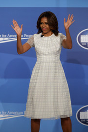 Michelle Obama wears a windowpane-printed white dress.