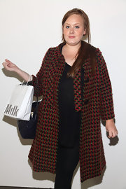 Adele wore a red and green tweed coat over her black ensemble for the Barbara Tfank presentation.