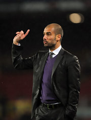 Josep wears a black blazer over a purple sweater dress at a soccer game in Spain.