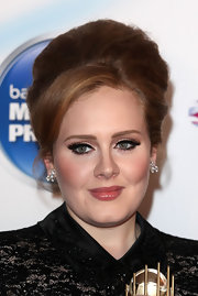 Adele accentuates her '60s cat eyes with false lashes.