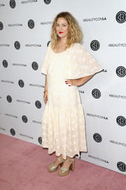 Drew Barrymore styled her dress with a pair of gold cross-strap platforms.