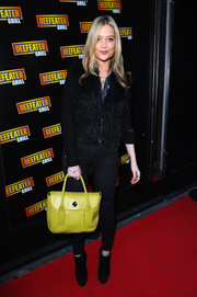 Laura Whitmore added a pop of color to her mostly-black outfit with a playful yellow handbag.