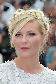 Kirsten Dunst wore her hair styled in a casually pinned updo featuring long side-swept bangs and a delicate gold flower-covered headband.