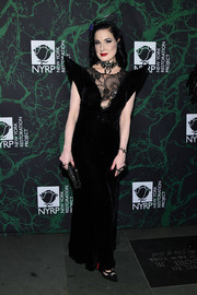 Dita Von Teese worked a pointy-shouldered lace-panel velvet gown at the 2017 Hulaween event.