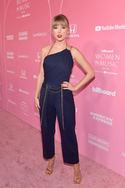 Taylor Swift looked chic and breezy in a navy Oscar de la Renta jumpsuit with an asymmetrical neckline and gold chain detailing at the Billboard Women in Music 2019.