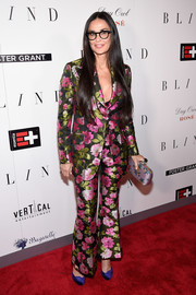 Demi Moore sealed off her look with a printed satin clutch by Gucci.