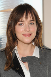 Dakota Johnson wore casual waves and wispy bangs along with barely-there makeup for a refreshing off-duty-celeb look during the Boss fashion show.